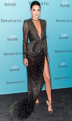 KENDALL JENNER wears a plunging, high-slit, long-sleeve black Redemption gown with a choker and Christian Louboutin heels to watch herself be projected onto the Empire State Building at the Harper's Bazaar 150th Anniversary Event in New York City.