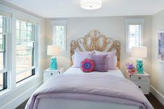 Restful purple and blue teen girl's bedroom boasts a wicker peacock headboard supporting a bed dressed in a lavender duvet paired with layered purple pillows lit by a white drum pendant.