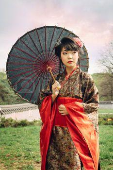 kimono japonais: Belle femme asiatique marchant dans le jardin et en kimono traditionnel japonais et un parapluie traditionnel Banque d
