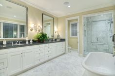 White Bathroom with Sconce Lights and Natural Stone Tile......   Elegant features such as the freestanding bathtub,with sharp lines glass shower in the transitional bathroom.