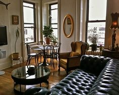 Dig the old world black leather, vintage sofa, and mirror, and bentwood dining set (and of course the tall ceilings and great windows...)