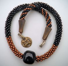 Guatemalan Black Jade is centered on this kumihimo necklace of copper and black beads. The cones and butterfly clasp are from www.handfast.biz