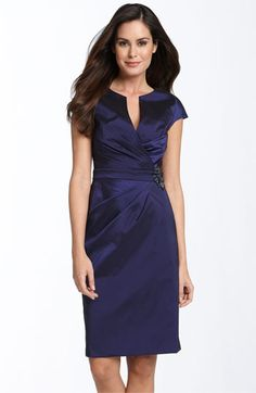 Pleats extend through the split neckline and skirt on a lustrous cap-sleeve dress, embellished with a collection of fabric-covered rhinestones at the inset waist.
