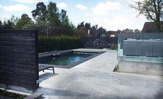 Poolmiljö med slipat betonggolv. Mörka poolväggar. Kompositträ som ram runt. Arkitektritad villa stockholm, rexplus.se
