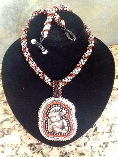 Monkey See, Monkey Do! Silver, red and black seed beads on spiral rope. Silver monkey focal with Ultra suede backing.