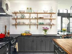 The homeowners replaced upper cabinets with open shelves and made bold use of inexpensive materials like standard subway tile, highlighting the existing chimney-style range hood and splurges like the honed black-granite countertops. | Cabinet paint: @SherwinWilliams Peppercorn | Countertops: @daltile