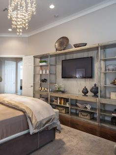 Jonathan Scott's bedroom includes a wall of vintage-style bookshelves showcasing art. A dazzling chandelier adds a touch of glam to the space.