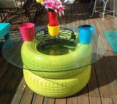 grün gestrichene Autoreifen und eine Glasplatte bilden den Couchtisch