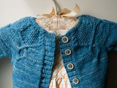 Pomander is a decorative cardigan to warm a special baby. The cabled swags trimming the seed-stitch yoke recall celebratory buntings, and optional subtle cables travel down the sleeves for a bit of extra style. The intricate details in this design make it at least an adventurous intermediate-level project, and you'll have to work from a chart for the yoke, but all symbols and techniques like the i-cord bind-off and provisional cast-on are fully explained with text or video links.