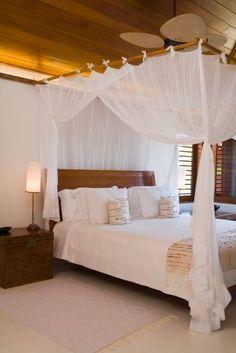 A ambientação da suíte máster acompanha o padrão do restante da casa: despojada e elegante. A cama com dossel de madeira e cortinado branco está em perfeita harmonia com o forro em réguas de madeira.