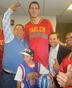 "From left: Mitch Modell; ""Tiny"" Sturgess, the all-time tallest Harlem Globetrotter at 7-foot-8; Leverage Agency President Ben Sturner; and fans in the locker room at halftime of the Globetrotters' Oct. 7 game at Barclays Center in Brooklyn. Photo by: TERRY LEFTON / STAFF"