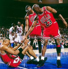 Michael Jordan and Horace Grant helping up Scottie Pippen