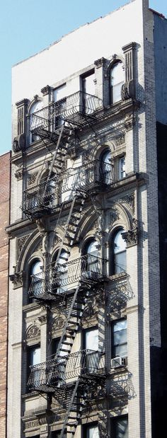 Windows, a fire escape and sculpture in East Harlem.