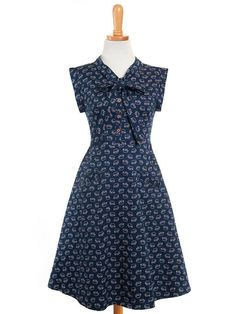 You'll feel cute as a button in this handmade dress, screen-printed with darling little elephants, tumbling on a navy background. The fabric tie at the neck and wide arm openings at the shoul…
