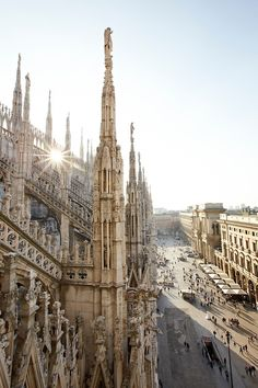 Images from the roof of the Duomo in Milan, with pedestrians walking through Piazza Duomo below. The roof of the duomo, the world's third-largest church, has more spires than any other cathedral in the world. It is possible to pay for an elevator ride to the roof, or for a reduced rate take the stairs.
