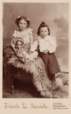 Antique photo of children with their doll.