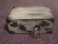 """DIY jewelry box How to: 1. Buy cheap """"treasure chest"""" box (mines from Walmart)  2. Paint/stain black 3. Coat with glue 4. While glue is still wet, paint white over it OPTIONAL 5. To get the box really distressed, add some wax in patches to the box 6. Paint another light coat of white paint 7. Scrape wax off to reveal """"aged"""" patches 8. Tah dah!!! You can also add some cork board in the inside lid part like I did to hang earrings on too!!!! Treasure Boxes, Treasure Chest, Diy Jewelry, Jewelry Box, Hanging Earrings, Paint Stain, Buy Cheap, White Paints, Cork"""