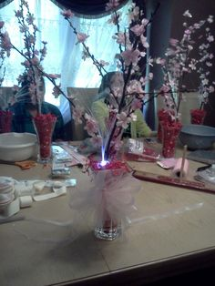 centerpieces...cherry blossom branch, red shredded paper, pearls, fiber optic strands and a beautiful bow!