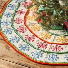 """HEIRLOOM COLORFUL SNOWFLAKES TREE SKIRT--Purchasing this beautiful hand-knit tree skirt helps support the Bosnian women, members of a fair trade collective, who create and sign each one. Wool. Exclusive. Size may vary slightly, as each is individually knitted. Approx. 59"""" dia."""