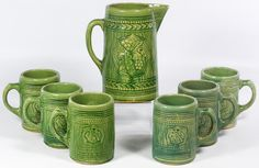 Lot 798: (Attributed to) Nelson McCoy Green Molded Stoneware Beer Set; Unmarked, having one pitcher and six mugs; all have leaf motifs