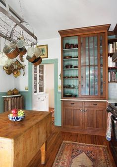 Turquoise kitchen interior of wooden cabinet highlights glaze on dishes