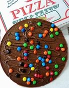 Featured on Food Network, our Chocolate Pizza blends rich milk chocolate with homemade English toffee for a taste masterpiece. This favorite comes topped with M&M'S® Candies. It is sealed and served in a genuine pizza box. Fun, delicious and a perfect gift for any occasion.