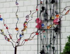 someone wound heavy gauge wire around a broom stick and stretched it out to create the branches for the tree. They then threaded various sizes and colors of glass beads on lighter gauge wire to attach it to the tree. Yard Art Crafts, Garden Crafts, Diy Crafts For Kids, Fall Crafts, Garden Art, Arts And Crafts, Craft Ideas, Garden Stakes, Glass Garden