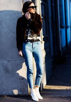 A leather-trimmed fur jacket is worn with a sweater, black belt, blue jeans, and white ankle boots
