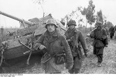 Tropas alemanas (nótese el hombre con una ametralladora MG42) desfilan junto a un carro Elephant destruido, marzo de 1944