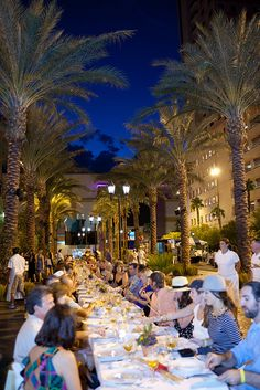 guests at community outdoor dinner event under the palms