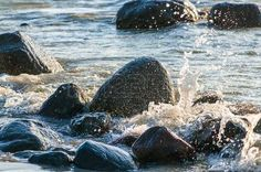 Large boulders on the beach, lapped by waves; Dark rocks in sea water