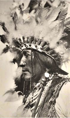 circa 1935 John Grounds wearing war bonnet, necklaces, and fur vest. Siksika