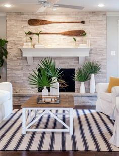 Oar paddles above the fireplace for wall decor in a coastal ranch home by Chip and Joanna Gaines: http://www.completely-coastal.com/2016/05/coastal-home-makeover-Chip-Joanna-Gaines.html