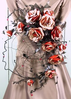 This beautiful bouquet is inspired by Bram Stoker's atmospheric masterpiece each rose is meticulously handcrafted from pages of the novel backed with a vivid red paper nestled into midnight shades of leaves.  The elegant crescent shape has provided a new home for a black widow spider who has woven her intricate web amongst the leaves.