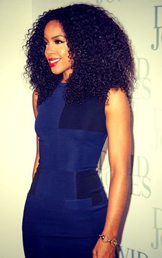 The beautiful Ms. Kelly Rowland with this nice full head of big curly hair and red lips. Wearing a very sexy blue bodycon dress.