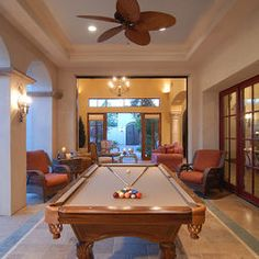 Covered patio with a pool table leads thru pocket doors into a smaller sitting room