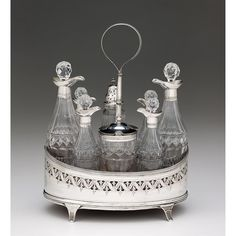 George III silver and glass cruet set  Peter & Ann Bateman, London, 1799-1800  Navette-shaped cruet with band of pierced and chased foliage and bellflowers, fitted with eight cut-glass and silver bottles, monogrammed.