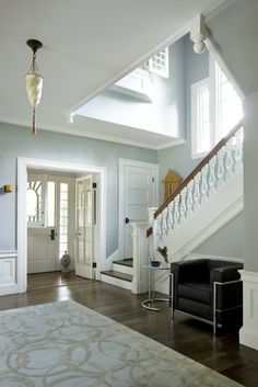 Entryway. Pale blue walls. TONS of natural light allows for dark wood floors, and stair banister.
