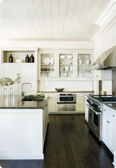 wide plank floors, white cabinets, dark counters, open cabinets, microwave below counter, white subway tile backsplash