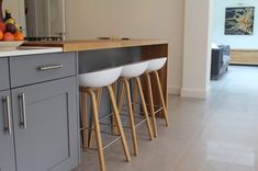 Island and units in Little Greene's Dark Lead. French Grey Mid on the tall cupboards on the back wall. The elegant wooden stools are from Hee Welling and Hay.