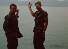 In this rare color photo we see two United States soldiers giving Vietnam the one finger salute as they are leaving to return home to the United States.