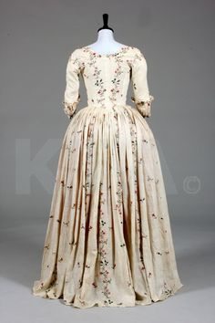 An embroidered lawn robe l'Anglaise, circa 1770-80, delicately embroidered in chain stitch with stripes and sprigs of pinks, convolvulus, dog roses, honeysuckle, tied with pink bows, closed-front bodice panels with drawstring to neck, the sleeves with shaped elbows adorned with ruffles; together with a pink taffeta petticoat of 18th century silk but 19th construction (2) Provenance: originally part of the Doris Langley Moore collection.