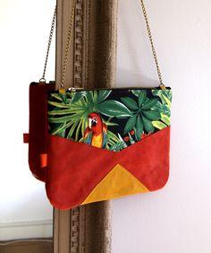 Sac à main en cuir souple, élégant et original.  Sac à main en cuir rouge et en tissus à motifs jungle. Il est composé d'une chaine de couleur bronze  pour la anse et d'une fermeture...