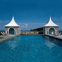 Two stone pool houses with arched white roofs flank each side of this Connecticut pool built close to the ocean.