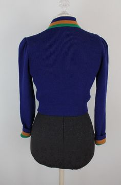70s Crop Sweater Fierceness - Royal Blue/Purple fine St. John knit sweater in a chic cropped style. Amazing little mustard and green bands on the cuffs and collar. The buttons are so unique and gorgeous. Excellent Vintage Condition Measurements taken flat. Double where appropriate.  Has some stretch. Bust- 16-20 in. Waist - 12-15 in. Length - 16.5 in. Estimated Size- Small, Medium, Large (depending on fit) 65 % Acetate 35% Nylon  ###All sizes given are estimates - please make sure to che...