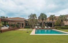 O paisagista Marcelo Bellotto projetou o extenso jardim com deque, que separa as piscinas rasa, infantil, e funda, ambas revestidas com pastilhas. O pergolado de cumaru fica em uma base elevada com spa. Projeto de arquitetura de Lica Cukier