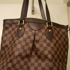 An oversized handbag great for traveling A dark brown with tan checkerboard print with gold tone accents Bags Travel Bags