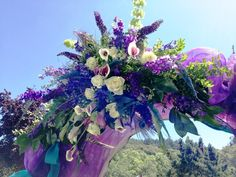 A wedding ceremony arch is decorated for a peacock themed wedding using blue and purple flowers with accents of teal burlap, and purple tulle. Wedding ceremony flowers and event decor from Seasonal Celebrations. http://www.seasonalcelebrations.com