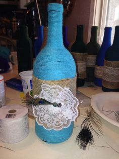 Matlock Wedding wine bottle wrapped with Turquoise yarn, peacock feather and lace.