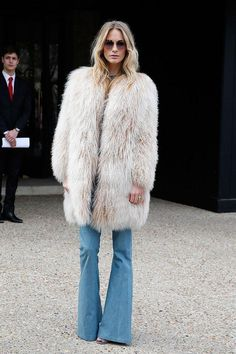 Poppy Delevingne channels Almost Famous with finger-raked curls, oversize square frames, a frothy pink fur jacket, and flared denim